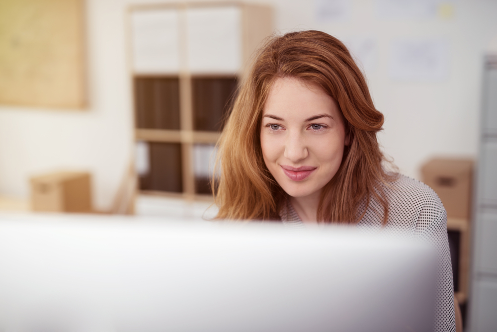 woman smiling while working on her computer