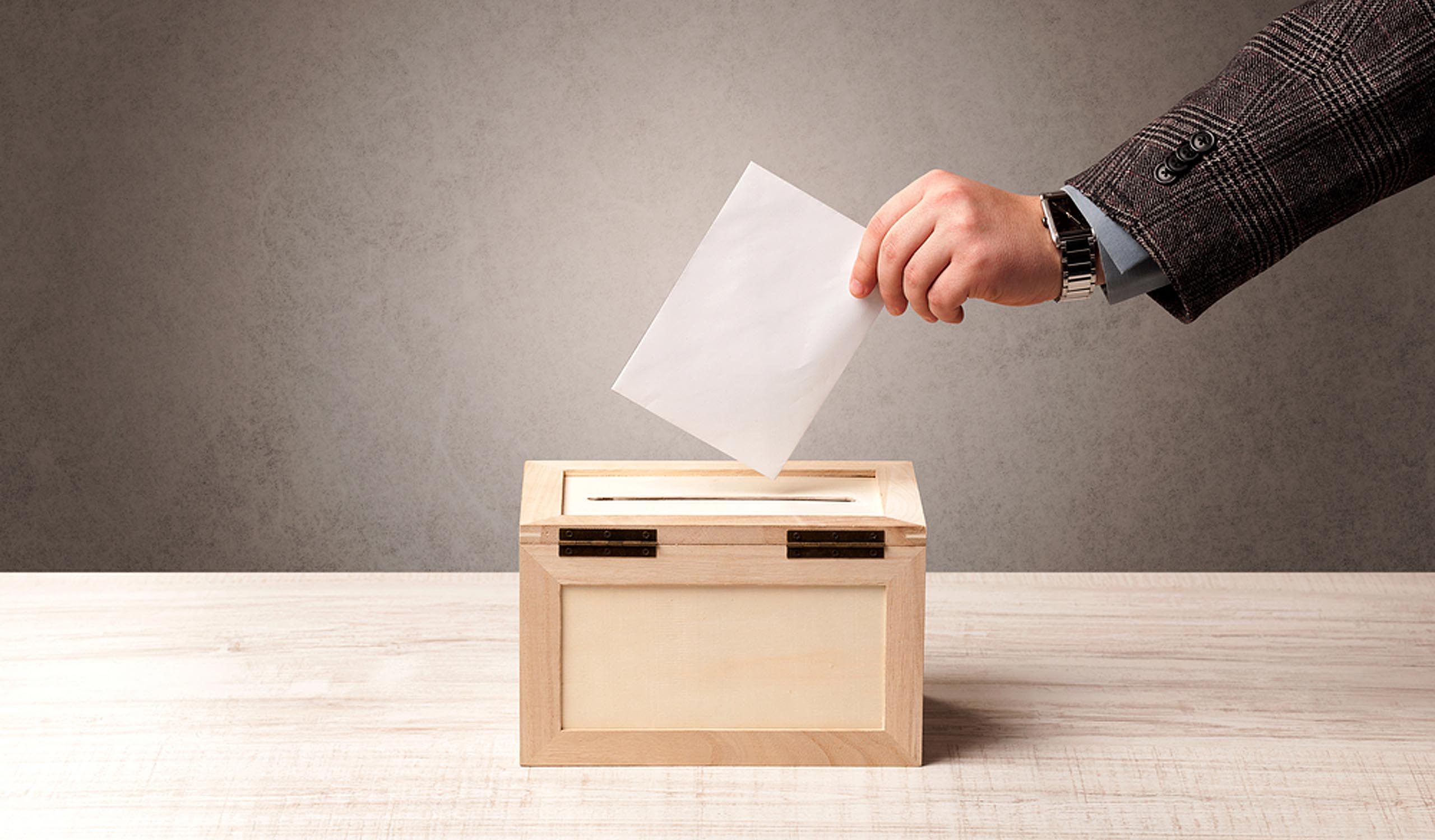 Ballot box with person casting vote on blank voting slip, brown wall background