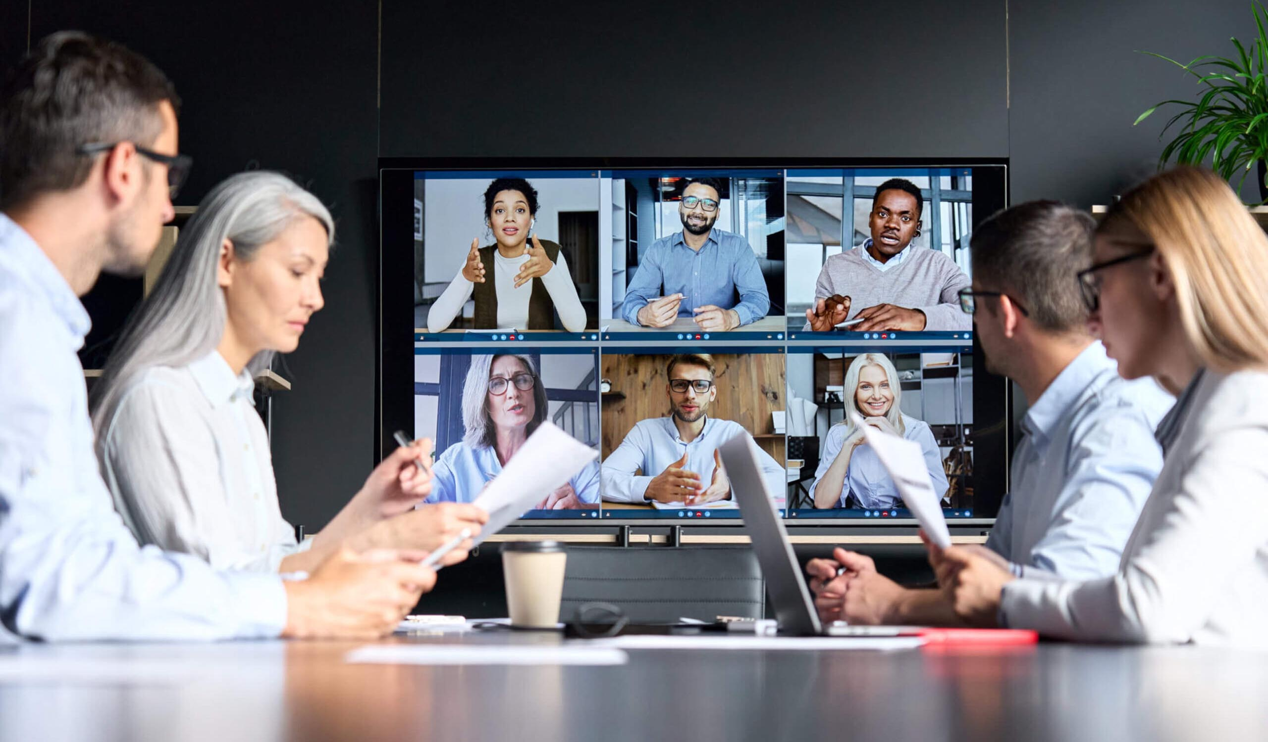 individuals having a hybrid meeting, half the team in person, half the team on a video call on a big screen in front of them
