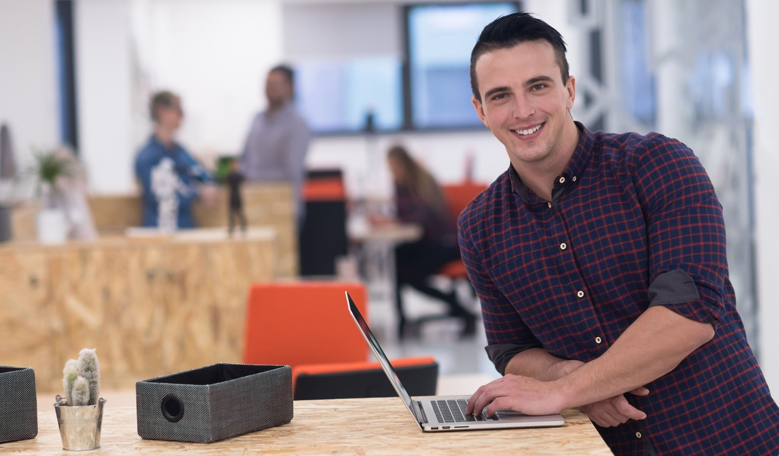 Man smiling while using his laptop at the office